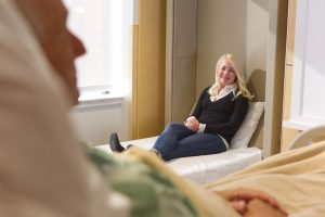 woman sitting on caregiver bed talking to father in hospital